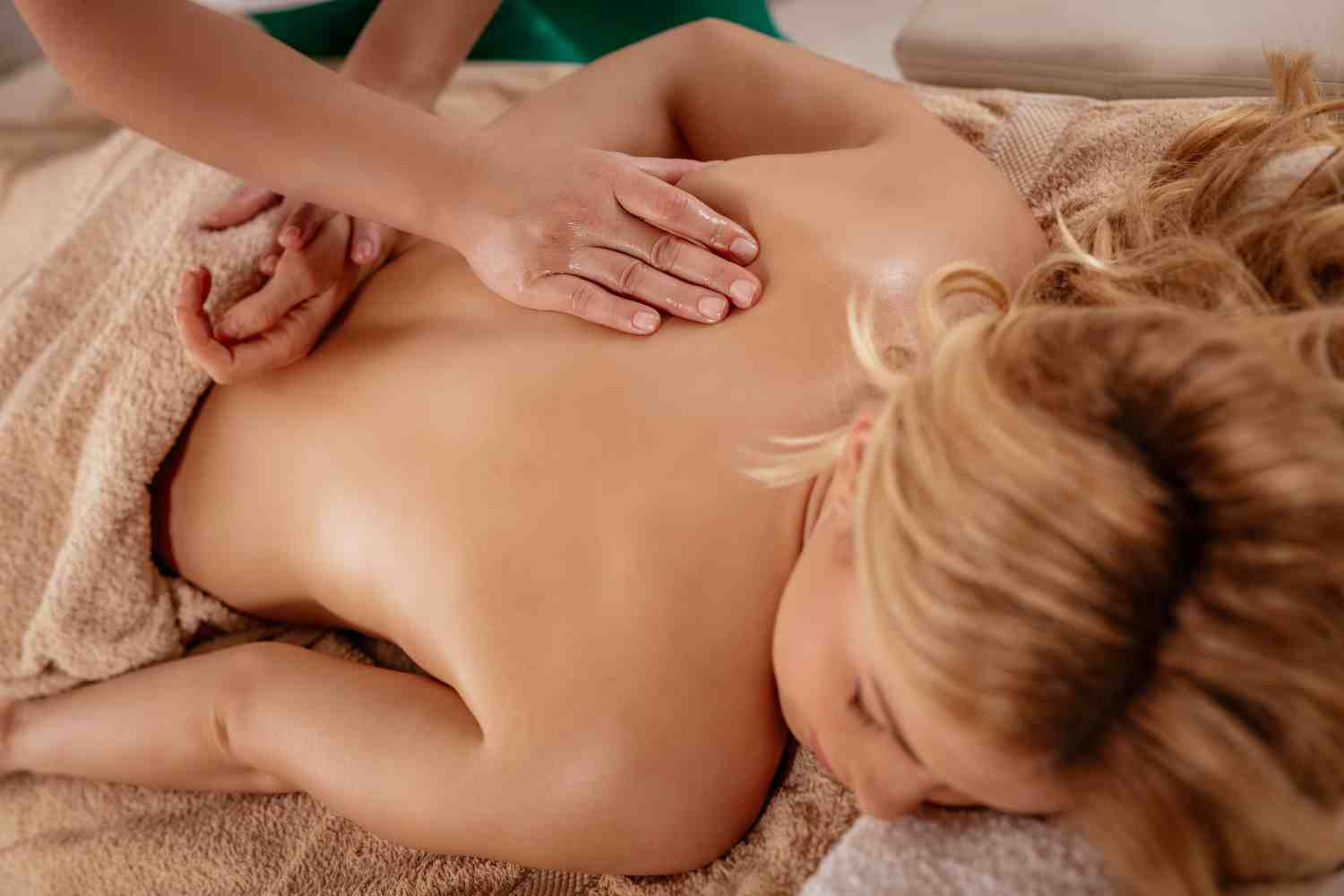 Massage therapist giving deep tissue massage to female