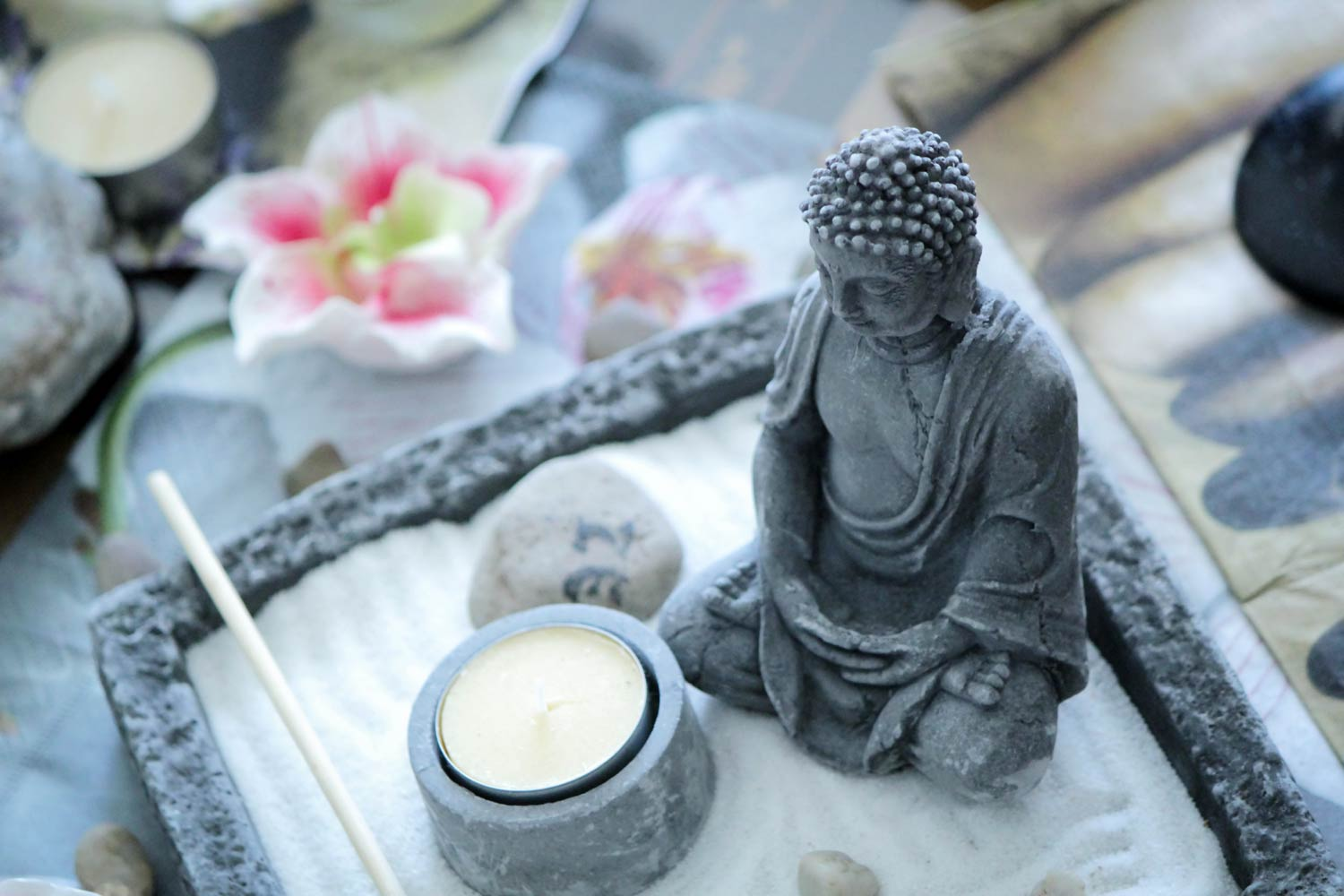 Asian Massage is represented by tranquil zen scene depicting statute in sand with candle and stone at Massage Fort Myers studio