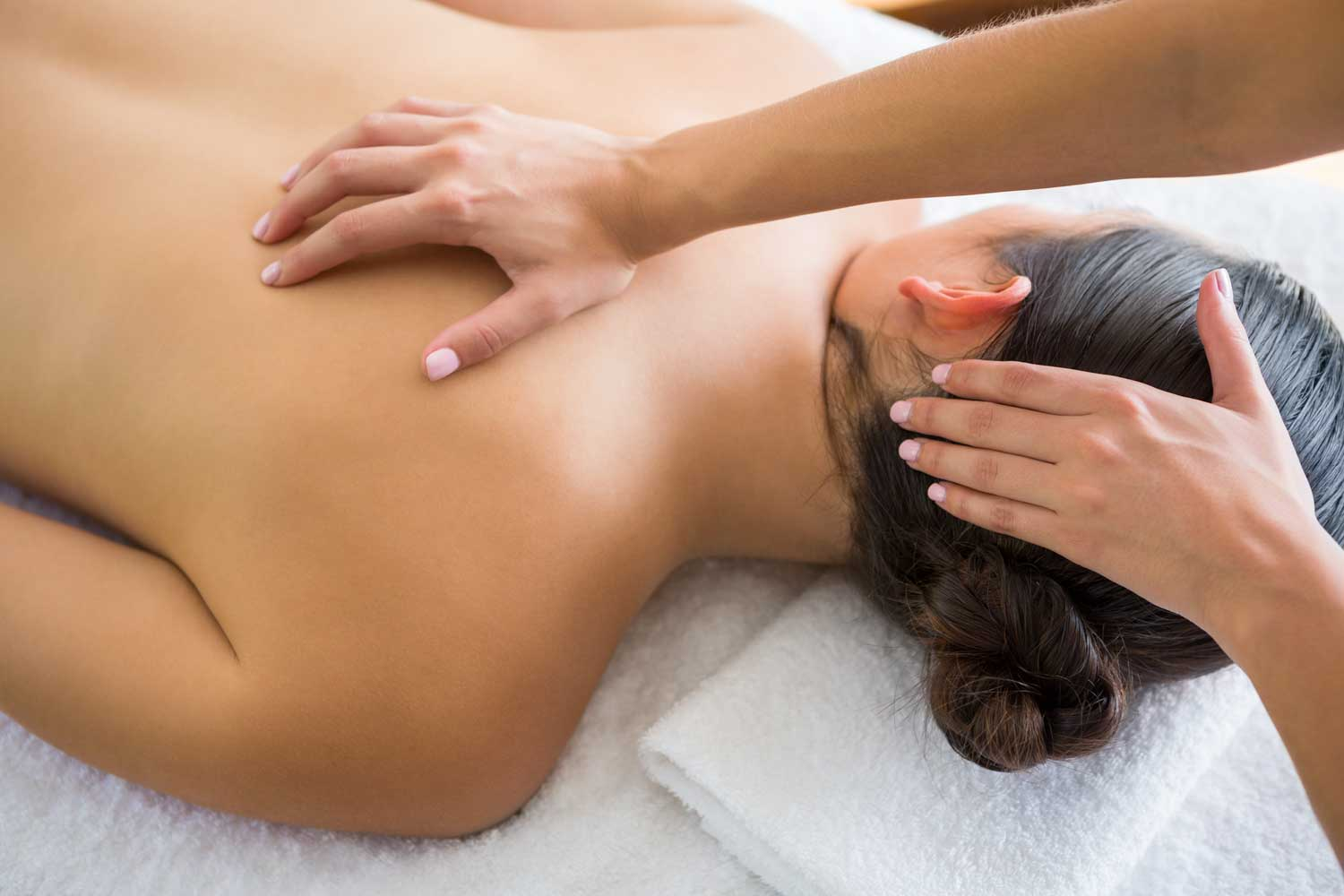 Massage therapist performing deep tissue massage on customer's neck and shoulder