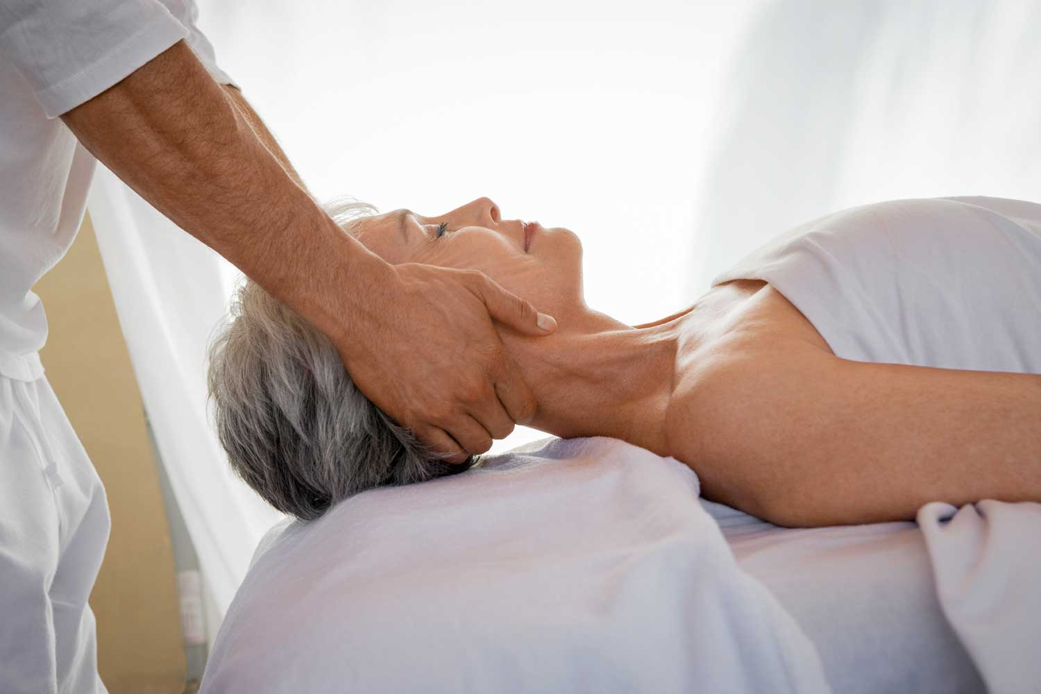 Geriatric massage is being performed on a mature client in a massage therapy setting