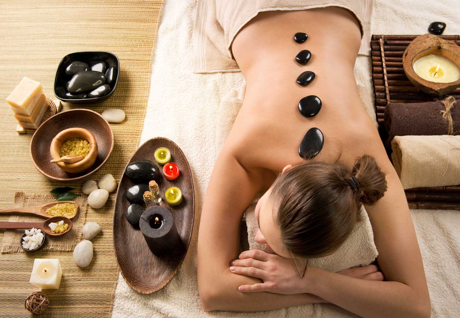 Hot stone massage is being performed on a female client in a spa setting