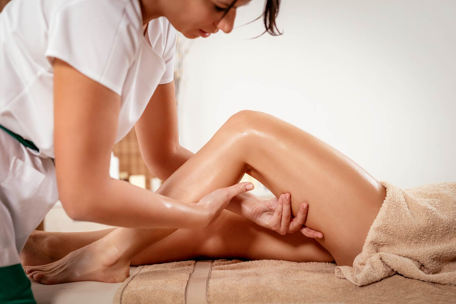 Lymphatic drainage massage being performed by a female massage therapist