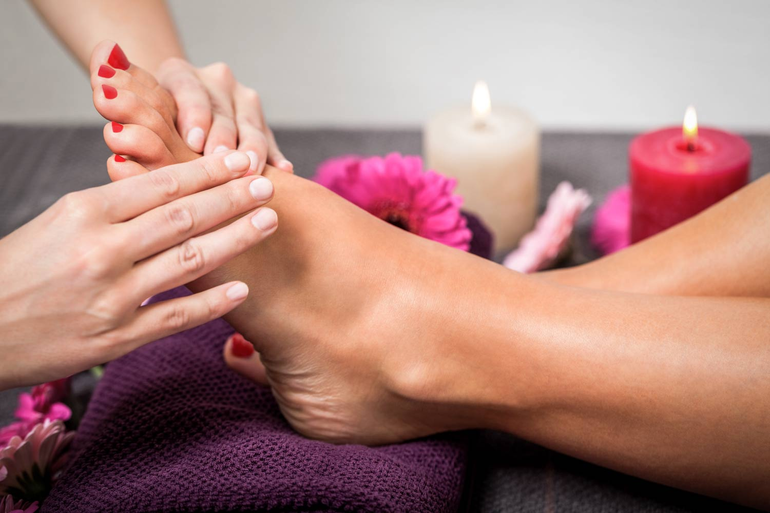 Foot reflexology is administered by female massage therapist in a spa setting