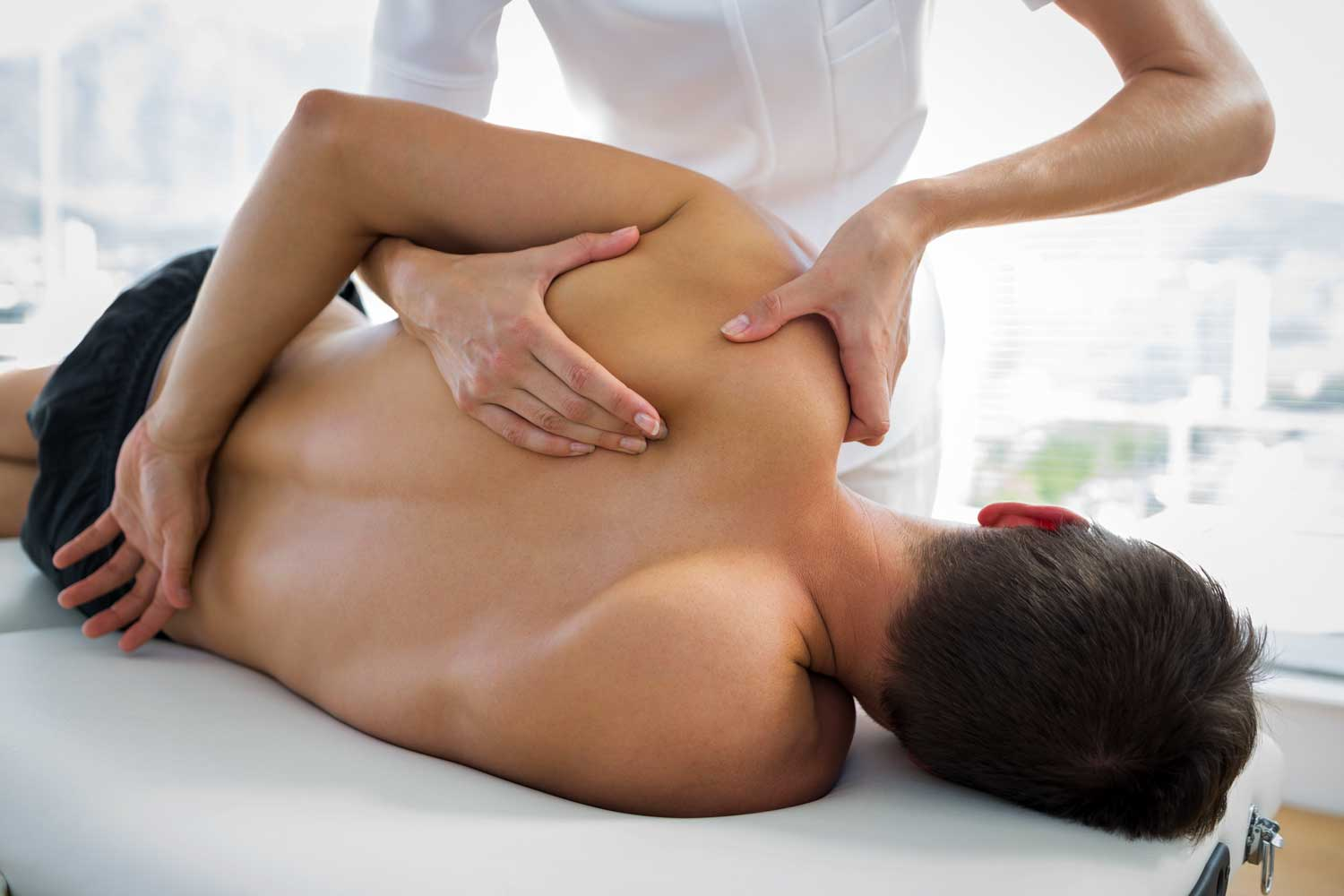 Thai massage is being administered by a female massage therapist